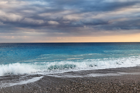The waves of the Mediterranean sea roll on the pebble beach in rainy weather. Sky and sea before the storm Standard-Bild - 113042275