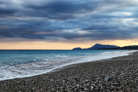 The waves of the Mediterranean sea roll on the pebble beach in rainy weather. Sky and sea before the storm Standard-Bild - 113042276