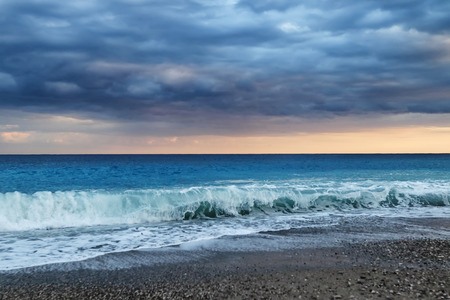 The waves of the Mediterranean sea roll on the pebble beach in rainy weather. Sky and sea before the storm Standard-Bild - 113042277
