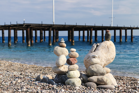 Sea stones of different sizes are built in a pyramid and keep balance. Coastal shoreline with views of the sea and pebble beach Standard-Bild - 113042280