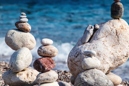 Sea stones of different sizes are built in a pyramid and keep balance. Coastal shoreline with views of the sea and pebble beach Standard-Bild - 113042282