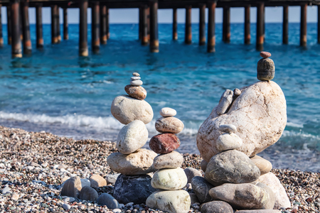 Sea stones of different sizes are built in a pyramid and keep balance. Coastal shoreline with views of the sea and pebble beach Standard-Bild - 113042281