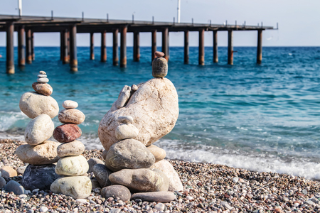 Sea stones of different sizes are built in a pyramid and keep balance. Coastal shoreline with views of the sea and pebble beach Standard-Bild - 113042283