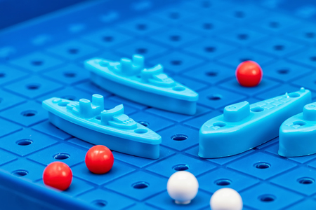 Toy war ships and submarine are placed on the playing Board in the game battleship