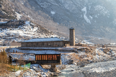 The building is a small cafe located in a mountainous area. The construction partially hangs over the bed of a small mountain river