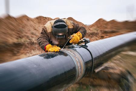 Le soudeur se monte dans la protection électrochimique du pipeline principal