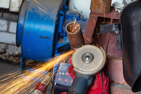 The welder carries out mechanical cleaning of the root surfaces of the weld seam to continue the weld multipass weld Banco de Imagens