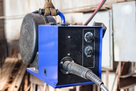 The device for semi-automatic welding in the environment of protective gases is suspended by the handle in the shop for convenience