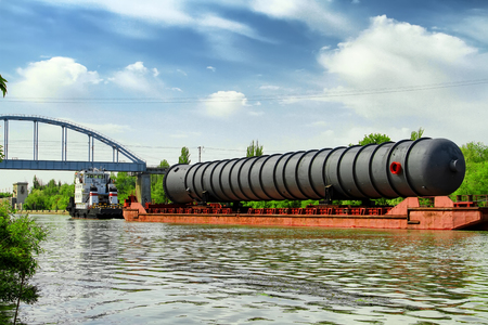 An oversized part of the column for the petrochemical industry on a barge on shipping canal