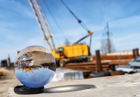 View of the base of building materials with a large yellow crane through an optical glass ball Foto de archivo - 122393415