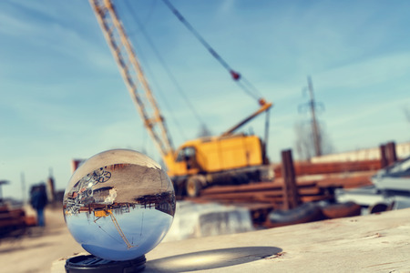 View of the base of building materials with a large yellow crane through an optical glass ball Imagens
