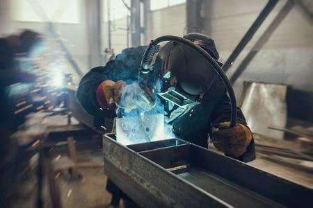 Soldador realiza trabajos de soldadura de estructuras metálicas en una posición espacial compleja soldadura semiautomática Foto de archivo