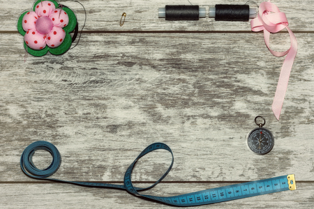 Buttons, ribbon , thread and needles for sewing . The concept of handmade sewing. On a light wooden background Foto de archivo - 122393022