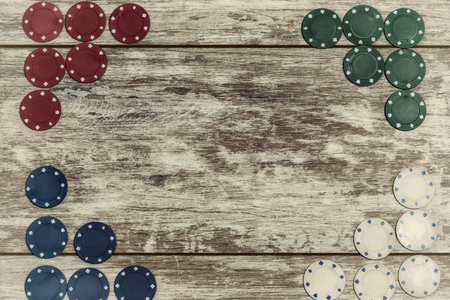 Las fichas de casino sobre un fondo de madera clara se colocan en los bordes con la capacidad de hacer una inscripción en el centro. El concepto de juegos de azar y casinos.