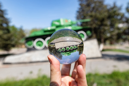 The monument to the Soviet t-34 tank stands on a high pedestal. Photos through a glass ball