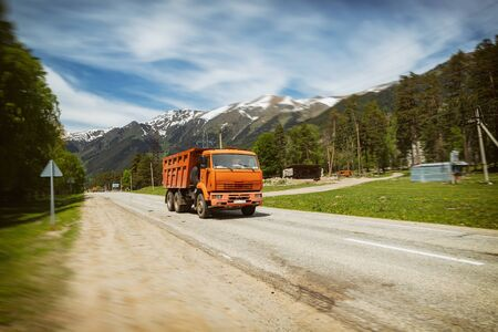 Orange road service truck rides on a mountain road. In the background is a mountain landscape with a peak and clouds