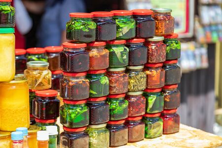 Small colorful glass jars with jam from local berries, herbs, roots and nuts on the counter of mountain traders 写真素材