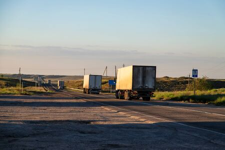 Trucks with different cargos go out of town for a bypass road 写真素材