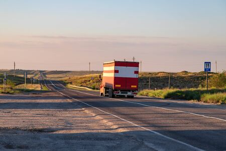 A large red truck transports goods on a long-distance road at sunset 写真素材