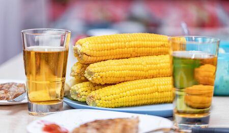 Light dinner for two : Boiled corn on the cob, roasted meat and beer in glasses
