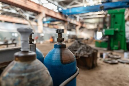 Gas cylinders for oxygen and argon are in a spacious , dark production shop Stockfoto