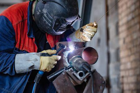Soldador en el taller muestra de soldadura del tubo para pasar la certificación. Soldadura por arco manual con mando a distancia