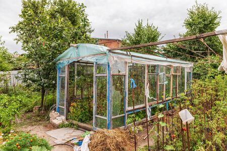 Construction of a greenhouse in the garden from scrap materials and old junk Standard-Bild - 129459760
