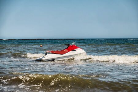 Red and white jet ski splashing on the waves near the shore.