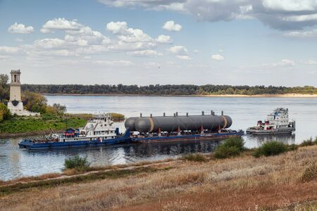 Transportation of large tanks for petrochemical enterprises by river on a special platform with help of two tugs