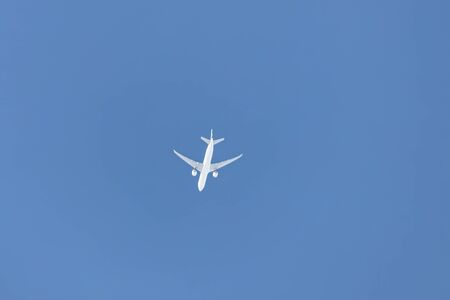 A small passenger plane with two turbines flies high in the sky