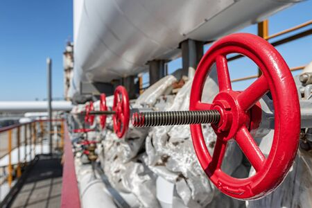 A number of new shut-off valves with red flywheels on the new hydrocracking plant