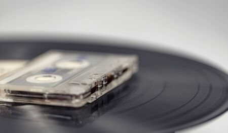 An old audiotape with a magnetic tape lies on vinyl record