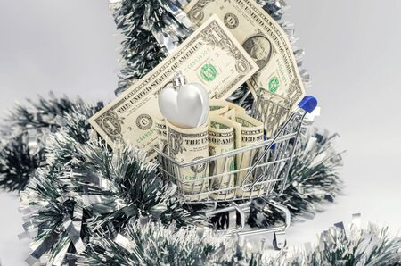 In a toy grocery cart are rolled up dollars and Christmas decorations