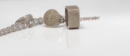 Different in shape silver rings with cubic Zirconia, silver bracelet and chain with elegant weaving on white reflect surface