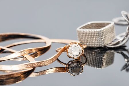 Gold and silver chains with snake weave, gold ring with gemstone, square silver ring with diamonds