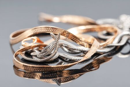 Elegant unusual silver chain and gold chain on reflecting surface