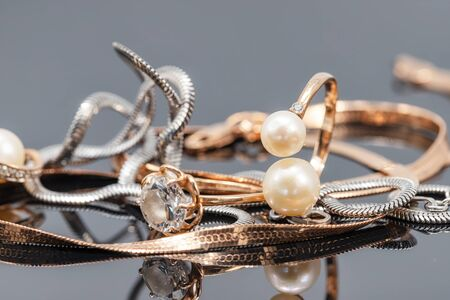 Gold rings with pearls and chains of gold and silver snake weave lie on a black reflective surface Stock fotó