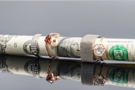 The rolled-up one-dollar bill wears silver and gold rings Stock fotó
