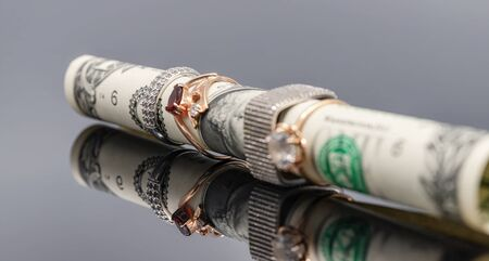 The rolled-up one-dollar bill wears silver and gold rings Stock Photo