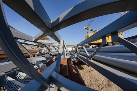 The section of metal structures ready for shipment lies on the production base under the open sky