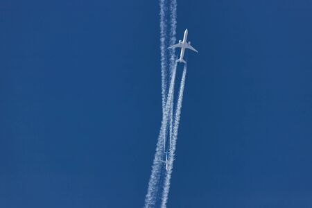 Two planes flying on opposite courses meet in the sky . View from the ground Foto de archivo