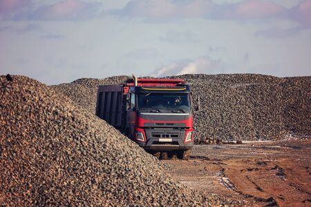 A large dump truck rides on the territory of the future construction of the highway against the background of large piles of rubble