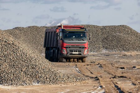 A large dump truck rides on the territory of the future construction of the highway against the background of large piles of rubble Stock Photo