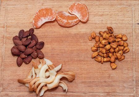 Wooden Board with different appetizers: fried almonds, smoked cheese and Mandarin slices Reklamní fotografie