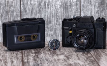 Technique of the 90s : an audio cassette player and a film camera on a wooden background 版權商用圖片