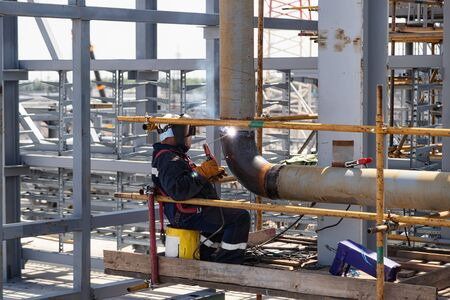 The welder performs the installation welding seam of the pipeline using scaffolding Standard-Bild