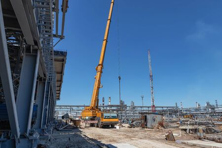 A large yellow truck crane stands ready to work on the construction site of the new plant