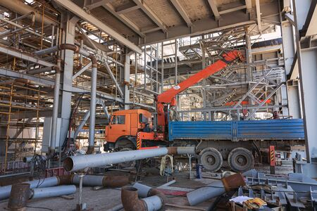 A mobile truck with a lifting boom stands inside a large factory shop under construction