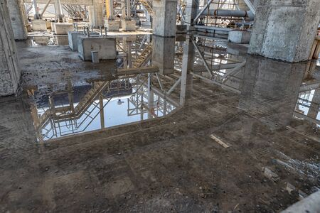 Large puddles after heavy rain on the open areas of the oil refining complex under construction