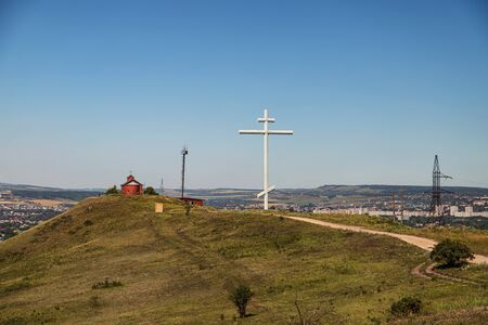 A large metal cross of worship stands on a hill at the site of the founding of the Cossack village in the Caucasus
